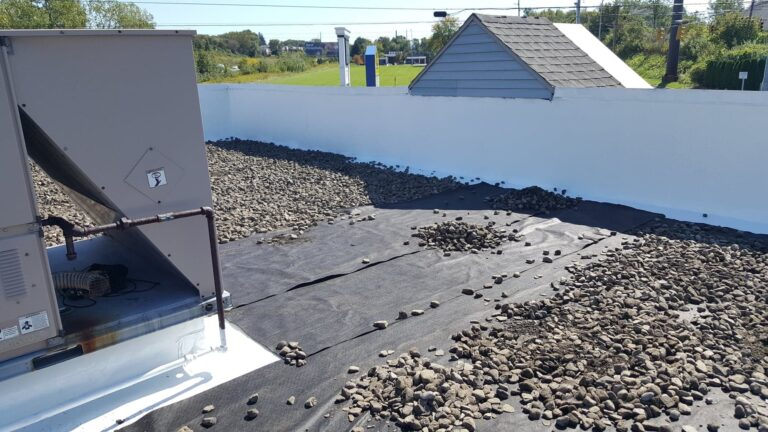 roofers applying ballasted stone over epdm membrane during the commercial ballasted epdm roof process